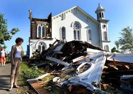 The steeple of the First Church of Monson Congregational lies on the ground, the clock frozen at the time of the devastation. Suzanne Kelley, Chairman of the Board of Trutees for the church, surveys the damage. (June 2, 2011)