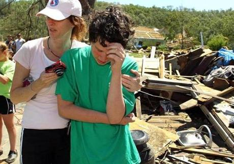 Joey Yarbrough cries while being comforted by a neighbor, Jennifer Silva, as a rescue crew searches the remains of his Stewart Ave. home for his dog, Riley. Riley was found under some rubble. (June 2, 2011)