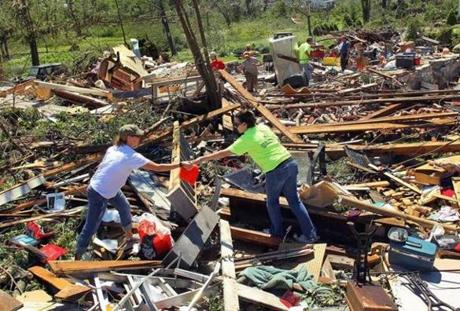 Daniell Thraser gives documents to Nicole Brike that she found in her boyfriend's destroyed family home. (June 2, 2011)