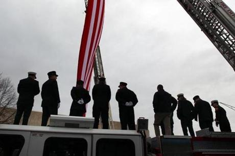 Danvers firefighters line the top of their aerial ladder tuck, displaying a huge American flag, during services for Peabody firefighter James M. Rice, in Peabody Square. (Dec. 30, 2011)