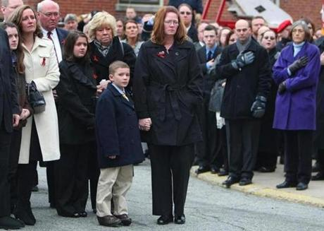 Ryan, 8, the son of the fallen firefighter and his wife,  Amy, watch as his casket is brought into the church.   (Dec. 30, 2011)