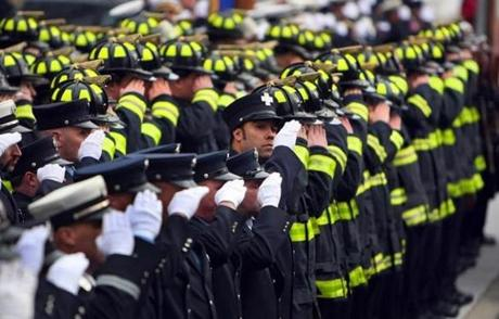 A sea of firefighters salute the casket of fallen firefighter, Jim Rice, in front of the church at the end of funeral services. (Dec. 30, 2011)