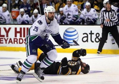 Nathan Horton lay on the ice, injured by a first period hit by Vancouver's Aaron Rome, who skates past Horton. Horton was removed on a stretcher, suffering a concussion. (June 6, 2011)