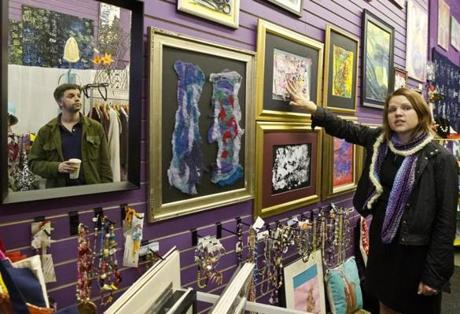 5/13/12 Somerville, MA Anyahlee Suderman (cq) manager of the Creative Union Gallery looking at a relief block print created by a visually impaired artist, Bob Spezzaferro (cq) as Tim Devin (cq) the founder of the Somerville Stock Exchange (mirror) looks at the art work at Creative Union Gallery on Sunday May 13, 2012. (Matthew J. Lee/Globe staff) slug: 24nostock section: nowk Reporter: Susan Johnston