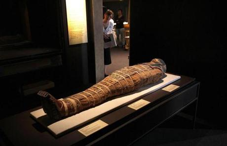 BOSTON ,MA 05/ 22/ 2012 : LOOKING OVER the mummy in its resting place from a doorway is Rebecca Barber (cq), an intern with Peabody Essex Museum who helped work on the exhibit. LOST EGYPT: Ancient Secrets, Modern Science exhibit at the Museum of Science in Boston opens this month. ( David L Ryan / Globe Staff Photo ) SECTION: METRO TOPIC stand alone photo