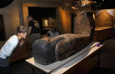 Intern Rebecca Barber looked over a coffin in the exhibit.