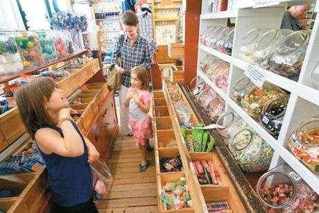 Rebecca Linn, 7, of Dennis, surveyed canisters of candy during a visit to Brewster General Store in Brewster with her sister, 6- year-old Emily, and a family friend, Stacy Ferguson of Manchester, N.H. The shop is a popular spot for tourists.