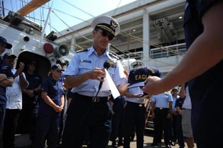 Captain Eric Jones presents a cap with the ship's name to a new crew member of the USCG Barque Eagle on May 28, 2012.