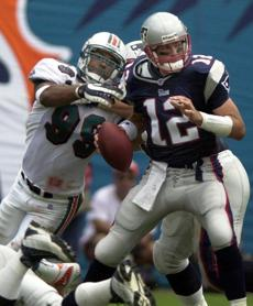 Tom Brady, pressured here by Jason Taylor, was 12-for-24 for 86 yards with no interceptions or touchdowns in his second career start.