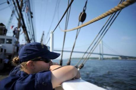 Cadet Sloane Hecimovich of Milton, Wisconsin, takes in the sight of the fading New York skyline as the USCG Barque Eagle, a training ship, approaches the Brooklyn Bridge on May 28, 2012.