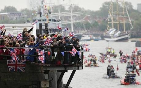 Crowds by the river cheered as the flotilla passes Tower Bridge.