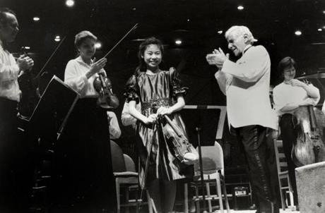 Midori, a then-14-year-old violinist, is applauded by conductor Leonard Bernstein after a performance with the Boston Symphony at Tanglewood on July 26, 1986. (Walter H. Scott/Courtesy Boston Symphony Orchestra Archives)