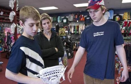 Comlax employee Chris Mackay, 20, talked lacrosse sticks with Nolan Holbrook, 13, and his mother, Shannon Holbrook, of Westwood on Friday.