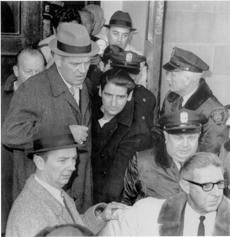 Feb. 25, 1967: Suspected Boston Strangler Albert DeSalvo, wearing sailor's garb, is shown leaving Lynn Police Station. His capture ended a nationwide manhunt begun when DeSalvo and two other inmates broke out of Bridgewater State Hospital the previous day. DeSalvo was captured at Simmons Uniform Co. at 741 Western Ave. He had spent the night in a nearby cellar and had found a sailor's pea jacket and trousers to replace his prison gear. He entered the store at 2:35 p.m. and asked salesman Frederick Waldron for permission to use the phone. DeSalvo told him,