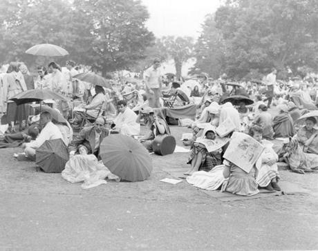 The lawn audience covers up with umbrellas, circa 1955.
