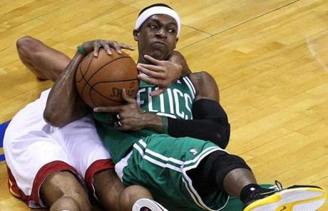 Rajon Rondo, shown being mugged here by Shane Battier, had 13 assists in 44 minutes for the Celtics.