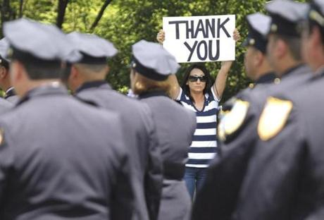 Springfield, MA - 6-8-12 - A woman holds a sign during the funeral procession for Springfield police officer Kevin Ambrose (cq) at St. Catherine of Sienna Church. (Globe staff photo / Bill Greene) section:met, reporter:knothe, Topic: 09funeral