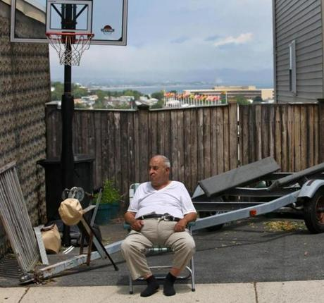 BOSTON ,MA 06/ 07/ 2012 : Eddy Matarazzo (cq) 84 yrs old sits in front of his driveway with the Suffolk Downs Race Track in the background over the fence. East Boston for profile of the neighborhood in light of proposed casino at Suffolk Downs. Focus on how neighborhood has changed, how the casino could take it in a new direction, and how opinions on casino track by background. ( David L Ryan / Globe Staff Photo ) SECTION: METRO TOPIC 10eastboston