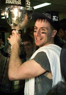 Hamilton Tiger Cat Darren Flutie hold up the Grey Cup as he celebrates his teams victory over Calgary Stampeders at B.C. Place in Vancouver, Sunday, November 28, 1999.(AP Photo/Chuck Stoody) Merlin Photo