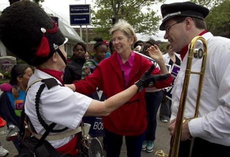 Elizabeth Warren greeted Providence Brass Band members Barbara Kuzdzol (left) and Dan Gabel, before marching in the Dorchester Day Parade.