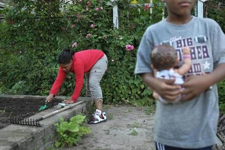 Ghiyahna Ennis, 11, tends her garden plot, which she shares with her sister and a friend on the street. The boy on the right is a cousin Timari Taylor, 6.