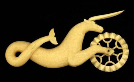 A pie crimper carved of walrus ivory in the form of a hippocampus.