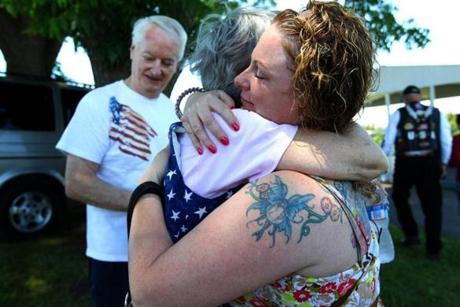 Marine Corps veteran Natasha Young-Alicea of Haverhill hugged Evelyn Harris as she met the parents of Navy SEAL Joshua Harris, for whom her service dog is named in Lexington, N.C. June 15, 2012.