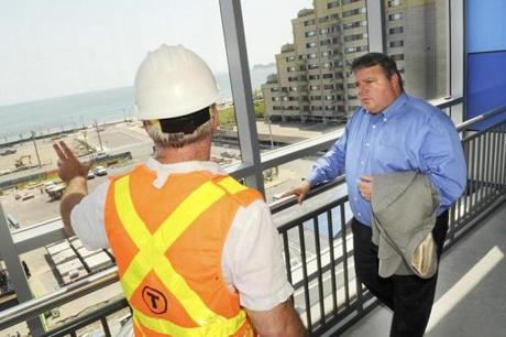 Project manager Tom Rovero (left) chats with Revere Mayor Dan Rizzo in the T's new Wonderland Station garage. Rizzo hopes to fill up Revere Beach with new residents, a hotel, and an office building, and has hopes for the former dog track.