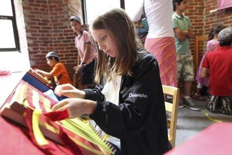 Courtney Christopher, 10 of Bedford, N.H., tries her hand at weaving while at the Lowell park's visitor center.