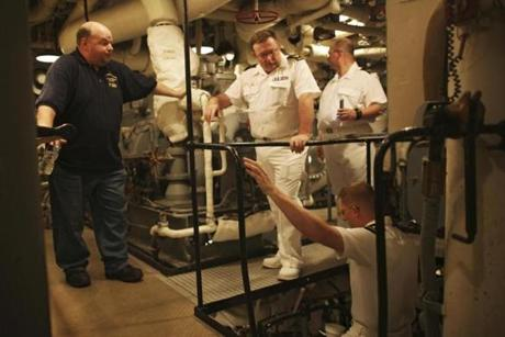 Bob Harris (left), a volunteer tour guide, gave a tour of the boiler room to seamen aboard the USS Cassin Young. More than 62,000 people toured the ship from January toMay of this year.