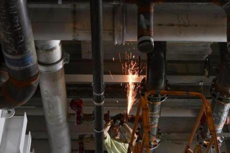 A welder cut a water pipe inside the Massachusetts Green High Performance Computing Center, which will use hydropower and other energy-efficient technologies.