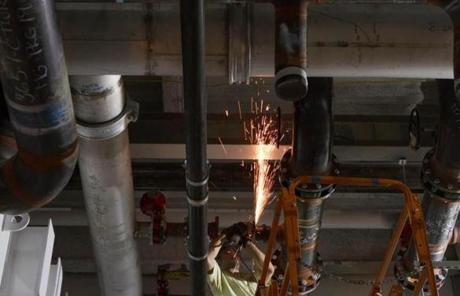 A welder cut a water pipe inside the Holyoke center, which will use hydropower and other energy-efficient technologies.