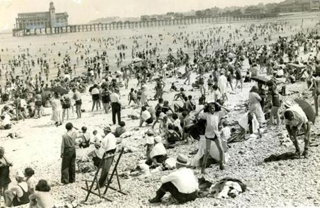 August 18, 1935: Revere Beach during a hot afternoon in August. Temperatures this day soared to 90 degrees and people in all manner of dress, casual and formal, took to the beach for a little relief. In its heyday, more than 250,000 bathers would relax along Revere Beach's shores on hot summer days. Seen in the background is the new Ocean Pier and Dancing Pavilion constructed in 1911.