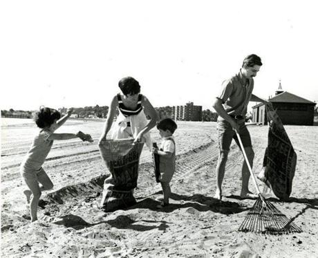 June 14, 1970 : Mr. and Mrs. Lewis Santosuosso and their children, Laura, 5,  and Lewis Jr., 2, cleaned Revere Beach at the start of the 1970 summer season.