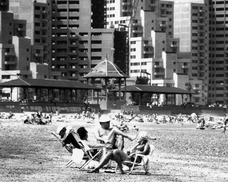 July 9, 1987: Sunbathers basked at Revere Beach as the contrast in decades is apparent in the background. The luxury high-rise condos have replaced the amusements and arcades once found along the boulevard. The beach area, ravaged by the Blizzard of 1978, saw a $130-million private and public redevelopment project build apartments and condominiums near the waterfront.