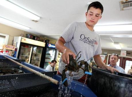 Justin Foley, 16, with James Hook & Co. in Boston, prepared a lobster to go.