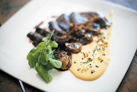Marinated skirt steak is nicely cooked, served with short rib ravioli and corn pudding.