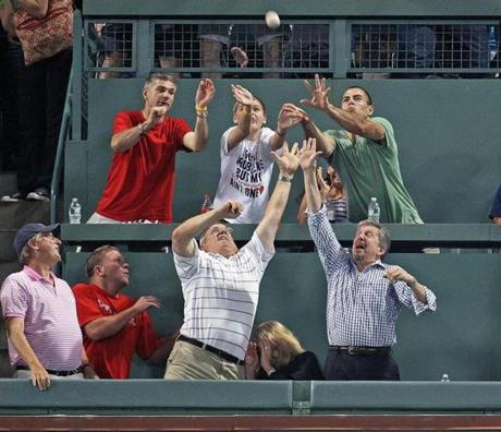 7-18-2012: Boston, MA: Fans in the Green Monster seats vie for the ball that the Red Sox Adrian Gonzalez (not pictured) has just hit for a fourth inning solo home run. The Boston Red Sox hosted the Chicago White Sox in an MLB regular season game at Fenway Park. section: sports (Globe Staff Photo/Jim Davis)