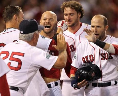 Dustin Pedroia, right, appeared ready to share a high-five with Bobby Valentine (25) after the second baseman scored on Cody Ross' walkoff home run Thursday.