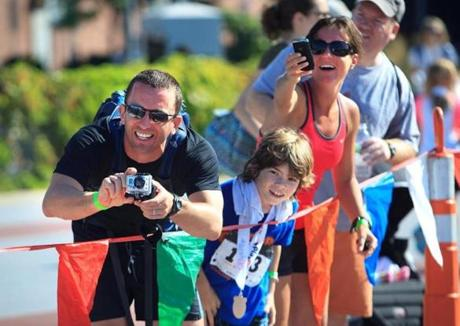 NEARING THE FINISH: Brian and Michele Martin of Wellesley, with neighbor Tyler Hinchley, 8, cheer as the Martins' 6-year-old son, Andrew, completes a kids' triathlon in Cambridge, MIT campus on July 22