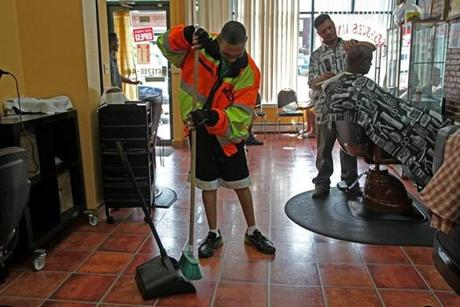 After lunch, Tata goes next door to the barber shop and sweeps up. Behind him is barber Candido Barros, who  chats with Tata while he works.