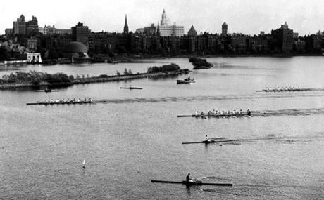 Single scullers watched the finish of the varsity race in the Compton Cup regatta on the Charles River on May 3, 1941. The Harvard Crimson shell (left) was victorious, the Princeton boat (center) finished second, and M.I.T (right) finished third. Named for the late Dr. Karl T. Compton, former president of M.I.T., the regatta began in 1933.