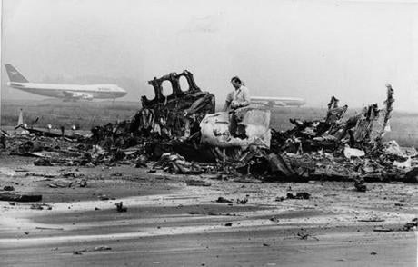 July 31, 1973: A rescue worker stood next to a section of Flight 723's charred fuselage. All 89 people aboard the wrecked Delta Airlines DC-9 jet, which crashed at Boston's Logan Airport, died. In the background, other planes prepared to take off.  The flight that preceded Flight 723 had made a successful approach and landed in the fog on runway 4R and the two flights that followed Flight 723, without knowledge of the accident, abandoned their approaches at the decision height because of weather. Those flights both landed safely in Providence, R.I.
