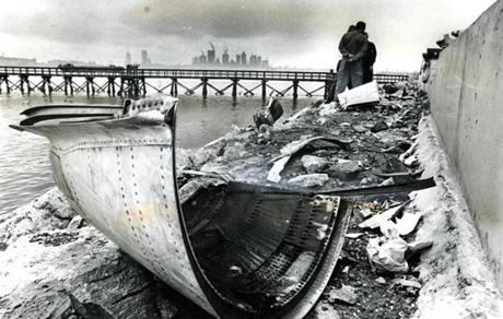 August 1, 1973: The Boston skyline was visible in the distance as investigators stood by the opening in the seawall on runway 4R. The aircraft had hit the three-foot-high seawall at the end of the runway. The plane departed from Burlington, Vt., and was originally due in Boston at 9:41 a.m. but made an unscheduled stop in Manchester, N.H. to pick up passengers who had been stranded there when a Delta flight to New York was canceled because of fog.