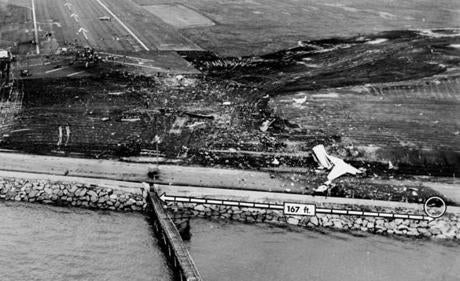 August 2, 1973: A hole (circle at bottom right)  was created when the DC-9 jet struck the seawall. It was 167 feet from the wooden pier on which landing lights were mounted, designed to guide incoming pilots to the end of Logan's runway 4R. The shattered tail section of jetliner lay beyond the wall.