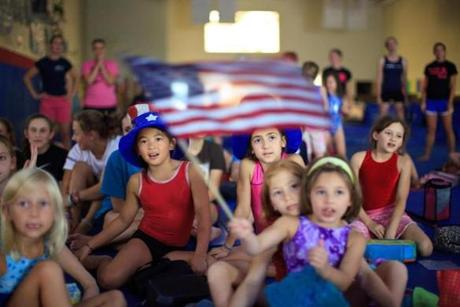 Shanna Lacey, 9, of Newton (red leotard); Katerina Poulopoulos, 9, of Medfield (pink leotard); Arielle Cohen-Oliveira, 10, of Newton (seated in front of Katerina); and Christina Dupre-Honda, 5, of Brookline (holding flag)  watched a live stream of the USA gymnastics team winning gold at the 2012 Olympics, during summer camp at the Exxcel Gymnastics & Climbing in Newton, where gold medlist Aly Raisman trained. July 31, 2012.