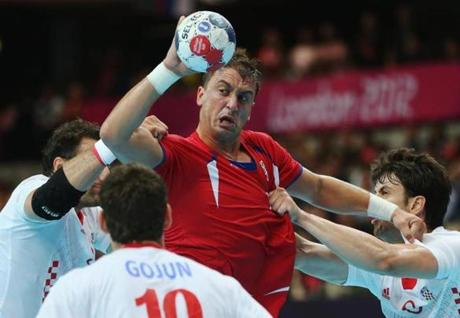 Momir Ilic of Serbia was challenged by Croatian defenders during a Men's handball match.