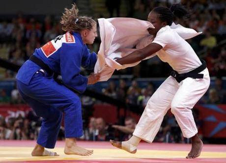 France's Gevrise Emane loses the top half of her judo gi as she fights with Israel's Alice Schlesinger (blue) during their women's -63kg repechage judo match at the London 2012 Olympic Games July 31, 2012. REUTERS/Toru Hanai (BRITAIN - Tags: SPORT OLYMPICS SPORT JUDO TPX IMAGES OF THE DAY)
