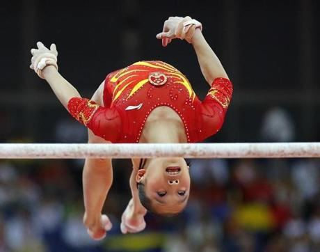 China's He Kexin performs on the asymmetric bars during the women's gymnastics team final in the North Greenwich Arena at the London 2012 Olympic Games July 31, 2012. REUTERS/Mike Blake (BRITAIN - Tags: SPORT OLYMPICS SPORT GYMNASTICS)