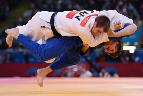 Canada's Antoine Valois-Fortier (white) competes with Russia's Ivan Nifontov (blue) during their men's -81kg judo contest quarter final match of the London 2012 Olympic Games on July 31, 2012 at the ExCel arena in London. AFP PHOTO / JOHANNES EISELEJOHANNES EISELE/AFP/GettyImages